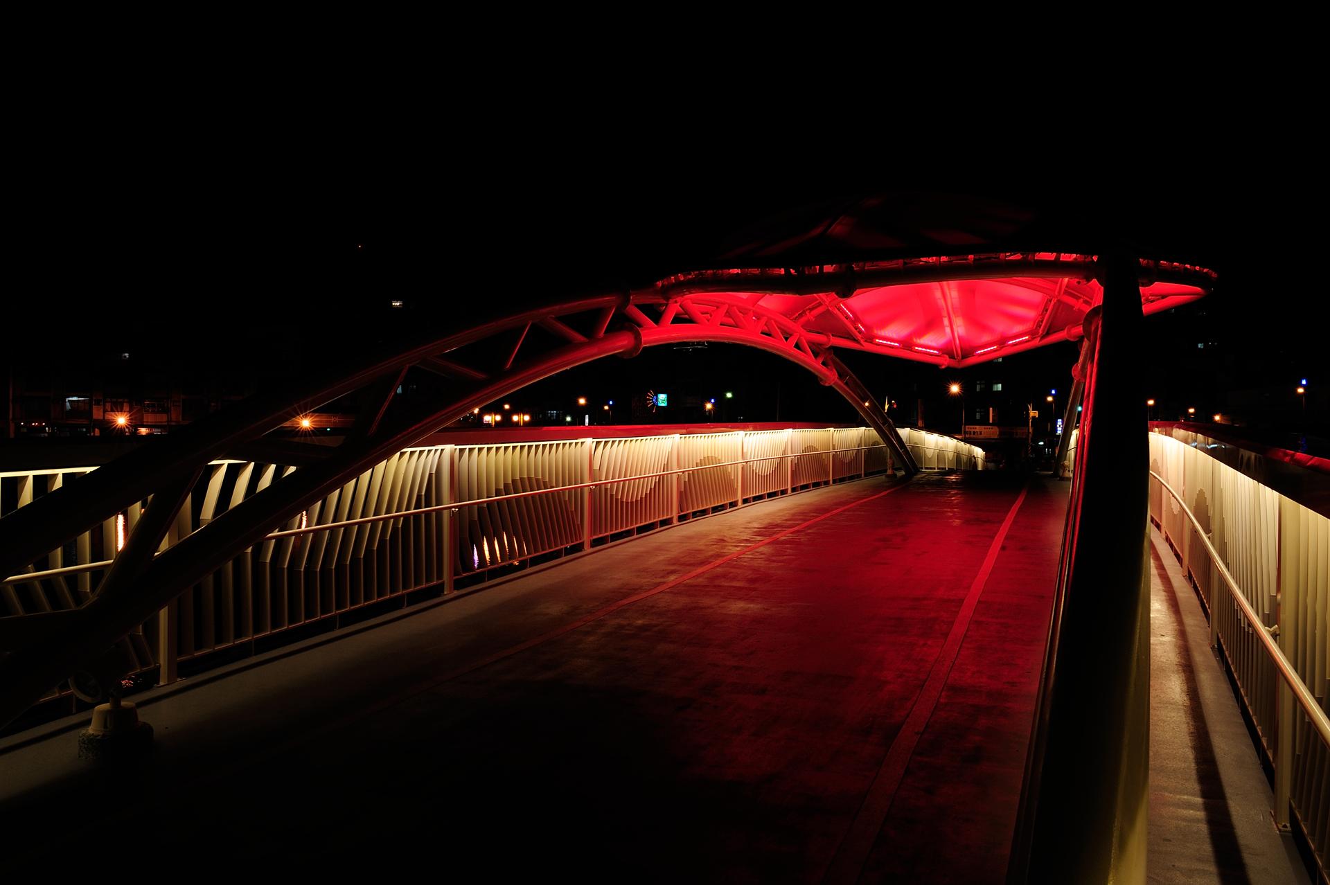 風景區內新建的金獅橋,是區內唯一一座限行人及自行車通行的橋樑,由於造型優美,橋中央還設有獨特的水瀑設施,使其成為風景區中的一大亮點,我司在得知橋樑的照明需求後,對於橋樑照明設計有豐富經驗的我們,協助得標的施工廠商調整裝在橋體上白色薄膜材質的多彩投光線燈,使其在夜晚中成為眾所矚目的焦點。紅色橋墩架以暖白色的線燈將其簍空的造型洗亮,張顯出其特色。欄杆部分同樣也以暖白光線燈洗亮,增加民眾行走的安全性,最後橋中央水瀑設施以多彩的燈色搭配水柱,營造出炫彩的水瀑,讓金獅橋在夜間展現出燦爛耀眼的光彩。